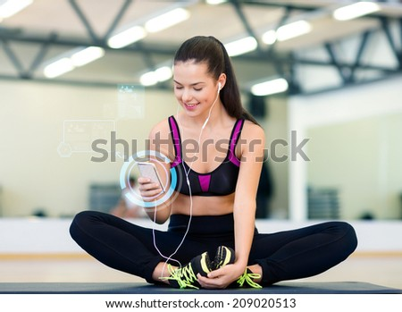fitness, sport, training, technology and lifestyle concept - smiling young woman with smartphone and earphones in gym - stock photo