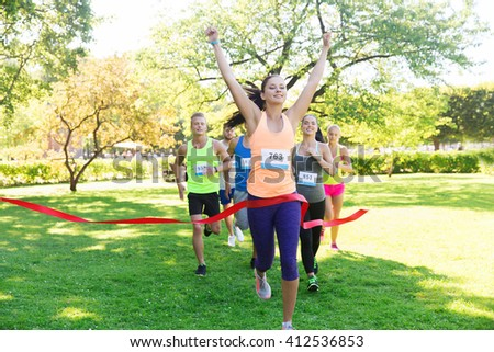 fitness, sport, victory, success and healthy lifestyle concept - happy woman winning race and coming first to finish red ribbon over group of sportsmen running marathon with badge numbers outdoors - stock photo