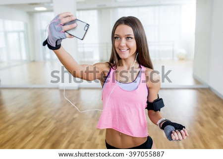 Fitness sporty sexy long hair girl making selfie photo on smartphone during workout break - stock photo