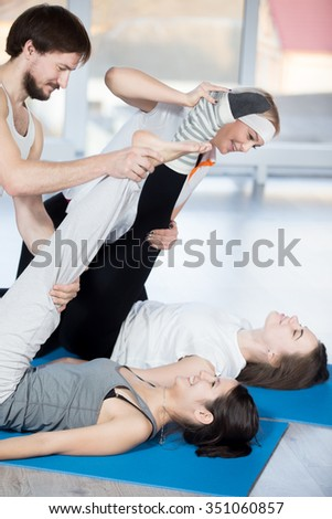 Fitness, stretching practice, group of four beautiful cheerful fit young people working out in sports club, doing exercises for hamstrings flexibility on blue mats, partners helping to deepen pose - stock photo