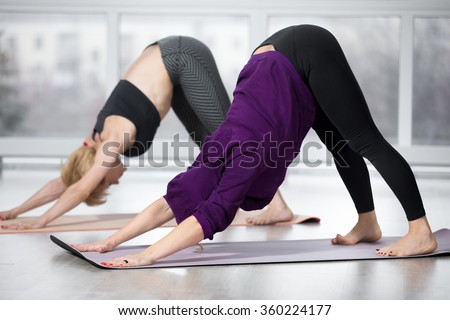Fitness, stretching practice, group of two attractive fit mature women in sportswear working out in sports club, doing downward-facing dog pose, adho mukha svanasana in class, full length - stock photo