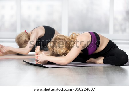 """Fitness, stretching practice, group of two attractive fit mature women working out in sports club, """"warming up"""", doing Head to Knee forward bend, Janu Sirsasana posture in class, full length - stock photo"""
