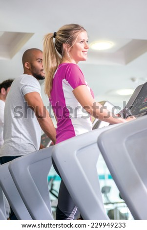 Fitness together on cross trainers. man and woman running on a CROSS TRAINERS - stock photo