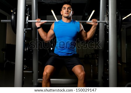 Fitness Trainer doing squats with barbells - stock photo