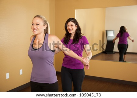 Fitness Trainer Helping Young Woman Stretch Before Workout - stock photo