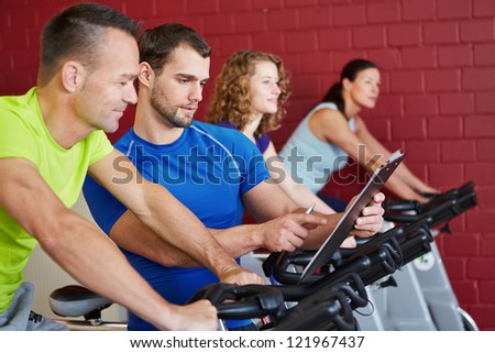 Fitness trainer with clipboard talking to a man on spinning bike - stock photo