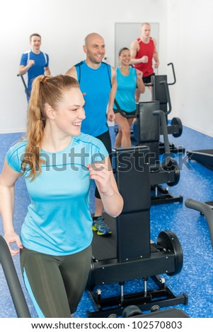 Fitness treadmill smiling woman enjoy group class at gym - stock photo