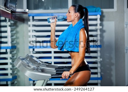 Fitness woman. Beautiful young girl in the gym on the treadmill drinking water - stock photo