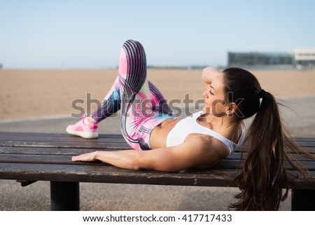 Fitness woman doing crunches exercise workout towards the beach. Female fit athlete training abdominal midsection for  improve core strength. - stock photo