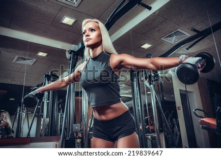 fitness woman doing exercises with dumbbell in the gym. Fitness girl in black sport wear with perfect body performing biceps exercises  - stock photo