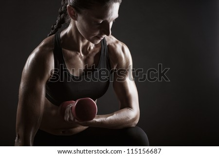 Fitness woman doing workout with weights on dark background - stock photo