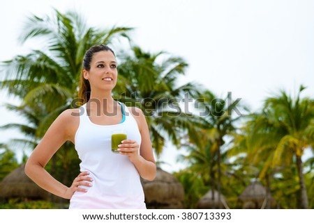 Fitness woman drinking green healthy detox smoothie at the beach on summer caribbean vacation. Female sporty girl taking a workout rest. - stock photo