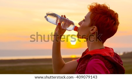 Fitness woman drinking water outdoors in park against golden sunset sky. Young girl drinking water after fitness run, jogger training at summer. Athlete sports drink from bottle nature outside. - stock photo