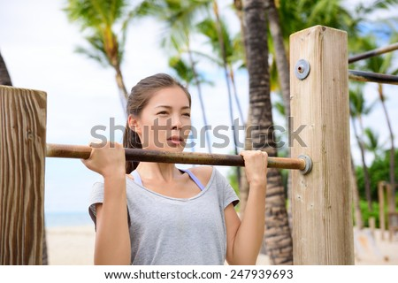 Fitness woman exercising on chin-up bar. Lady doing chin-ups training toned arms portrait outside on beach in summer. - stock photo
