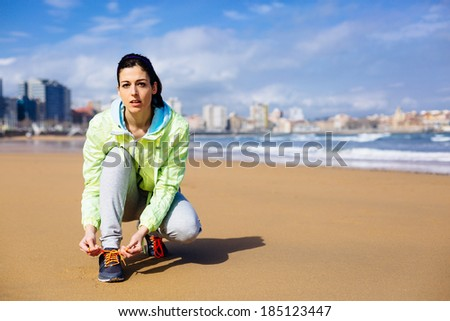 Fitness woman getting ready for running challenge at city beach in Gijon, Asturias, Spain. Female runner lacing sport shoes before training. - stock photo