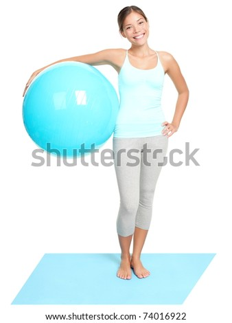 Fitness woman holding exercise pilates ball. Young sporty fit mixed race Asian / Caucasian female model standing isolated on white background in full length - stock photo