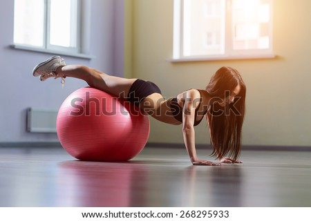 Fitness woman in gym resting on pilates ball. Young woman doing exercise on fitness ball. Young girl on the pink fitness ball in gym. Girl with fitness ball. Beautiful girl doing exercises with ball. - stock photo