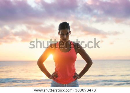 Fitness woman motivation. Challenging and motivating looking female athlete  with the sun and sea behind. - stock photo