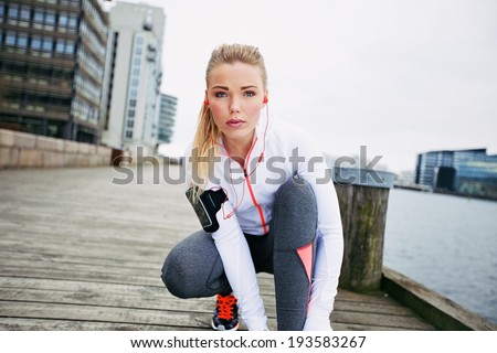 Fitness woman on boardwalk crouching to tie her shoelace looking at camera. Confident young female jogger training outdoors. - stock photo