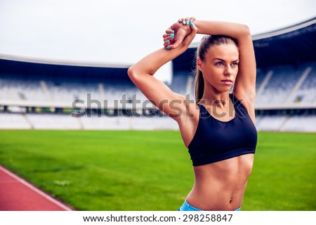 Fitness woman on stadium stretching - stock photo