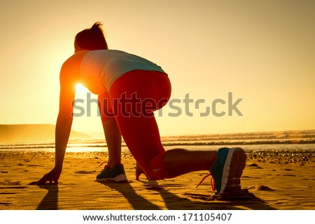 Fitness woman ready for running at sunset or sunrise on beach. Female athlete in powerful starting line pose. - stock photo