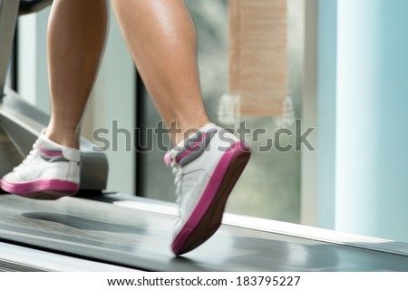 Fitness Woman Running On Treadmill - Close-Up Of Female Legs Running On Treadmill - Blurred Motion - stock photo