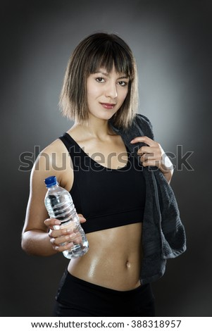 fitness woman shot in the studio low key lighting on a gray background holding water and a towel over her shoulder - stock photo