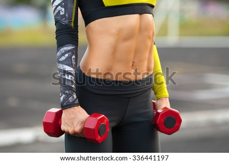 Fitness woman showing abs and flat belly. Muscular girl with dumbbels, shaped abdominal, slim waist - stock photo