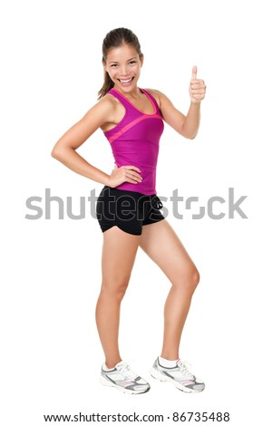 Fitness woman showing thumbs up success sign standing in running  outfit in full body isolated on white background. Healthy lifestyle concept of happy young mixed race Chinese Asian / Caucasian model. - stock photo