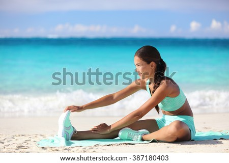 Fitness woman stretching legs on beach - Sporty Asian girl doing leg stretches, sitting one-legged hamstring stretch.  Happy young adult training her body on sunny summer tropical travel beach. - stock photo