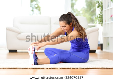 Fitness woman stretching legs sitting on the floor at home - stock photo