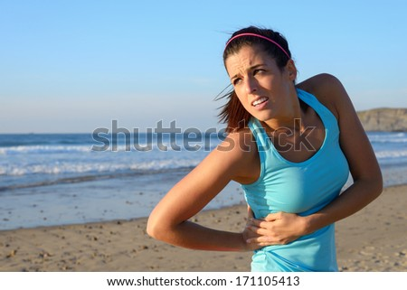 Fitness woman with side kidney pain. Female athlete with painful injury or spasm in serratus muscles. - stock photo