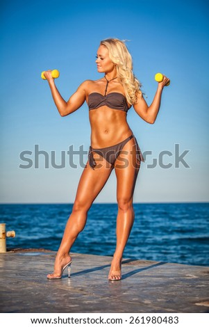 Fitness woman working out on beach in summer. Sporty girl training biceps hard with dumbbells. Sweaty sport caucasian female sportswoman - stock photo