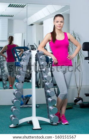 Fitness woman. Young beautiful girl doing sport exercises in the gym - stock photo