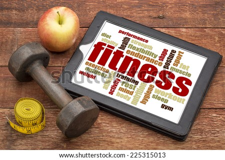 fitness word cloud on a digital tablet with a dumbbell, apple and tape measure - stock photo