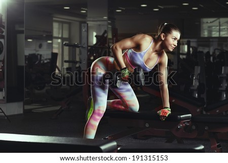 Fitness young sexy girl in the gym doing exercises with dumbbells - stock photo