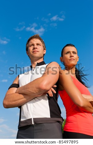 Fitness - Young sportive couple in front of a blue sky on a beautiful summer day outdoors - stock photo