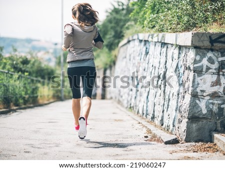 Fitness young woman jogging in the city park. rear view - stock photo