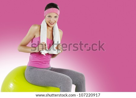 Fitness young woman with towel  around her neck smiling, she is sitting on pilates ball over pink background - stock photo