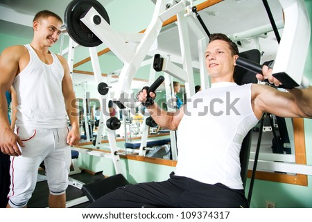 Fitness. Yung man at the gym doing arms exercises on a machine - stock photo
