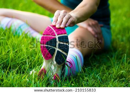fitt girl getting streching her legs before running outdoors - stock photo