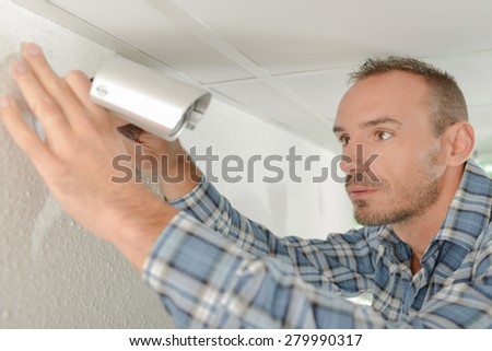 Fitting a security camera - stock photo