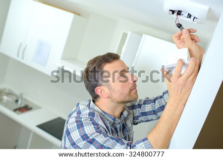 Fitting a smoke alarm in his home - stock photo