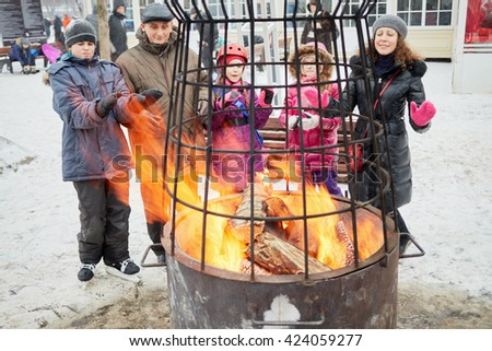 Five adults and children warm themselves at street fireplace in winter park. - stock photo