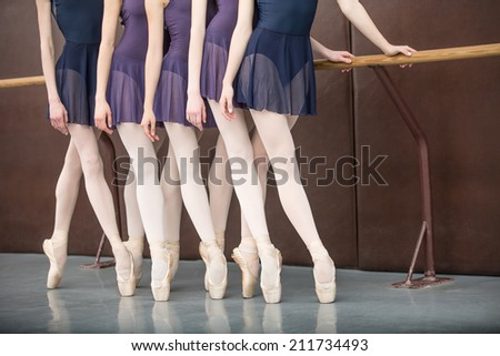 five ballet dancers in class near the handrail, legs only - stock photo