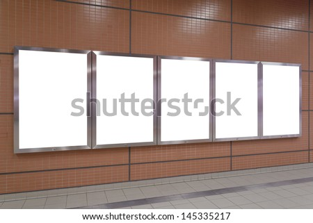 Five big vertical / portrait orientation blank billboard on brown wall - stock photo
