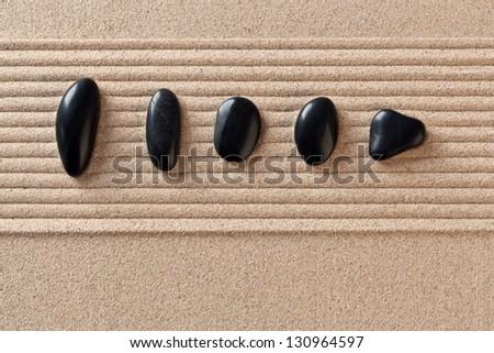 Five black pebbles on a raked sand zen garden. - stock photo