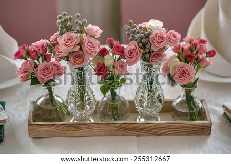 Five bouquets of roses on a festive wedding table in the restaurant. In the crystal and glass vases. - stock photo