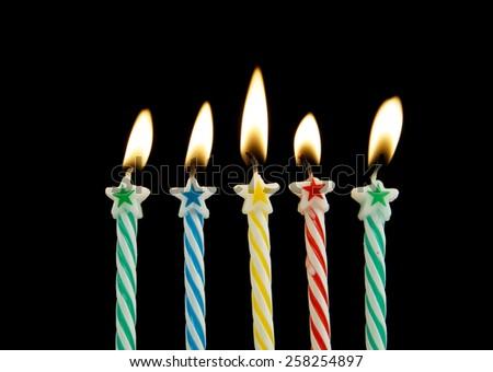 Five burning birthday candles on black background  - stock photo