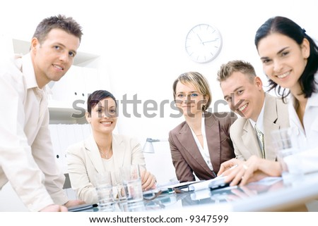 Five business colleagues sitting around table and working together, looking at camera, smiling. - stock photo